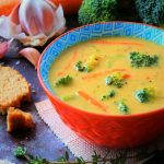 An angled head on image of a bowl of broccoli cheddar soup surrounded by fresh broccoli, carrots, cheese, bread and herbs.