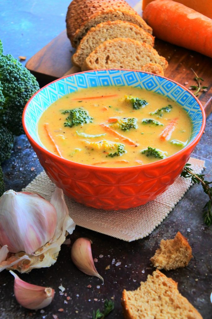 An angled head on image of a bowl of broccoli cheddar soup surrounded by fresh broccoli, carrots, bread and herbs.