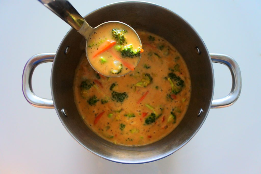 An overhead image of a pot of cheddar broccoli soup with a full ladle lifted out