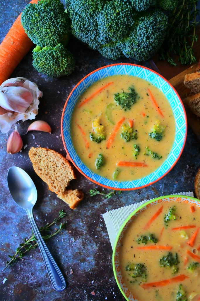 An overhead image of a bowl of broccoli cheddar soup surrounded by fresh broccoli, carrots, bread and herbs.