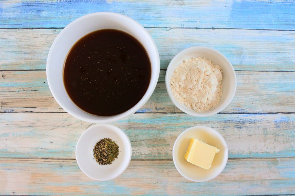 An overhead image of ingredients for a gravy including beef bone broth, whole wheat pastry flour, butter, black pepper and Italian seasoning.