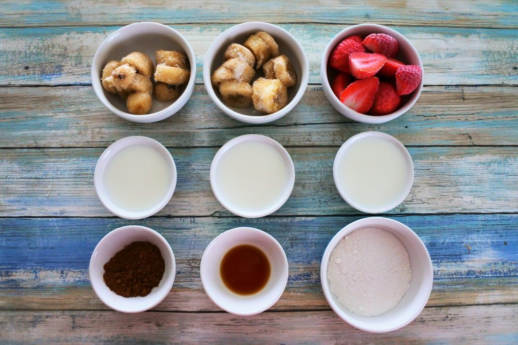 An overhead image of bowls of ingredients for the A composite image of the strawberry layer of the 6-Ingredient Neapolitan Milkshake including frozen bananas, frozen strawberries, milk, cocoa powder, vanilla extract and finely blended raw cane sugar