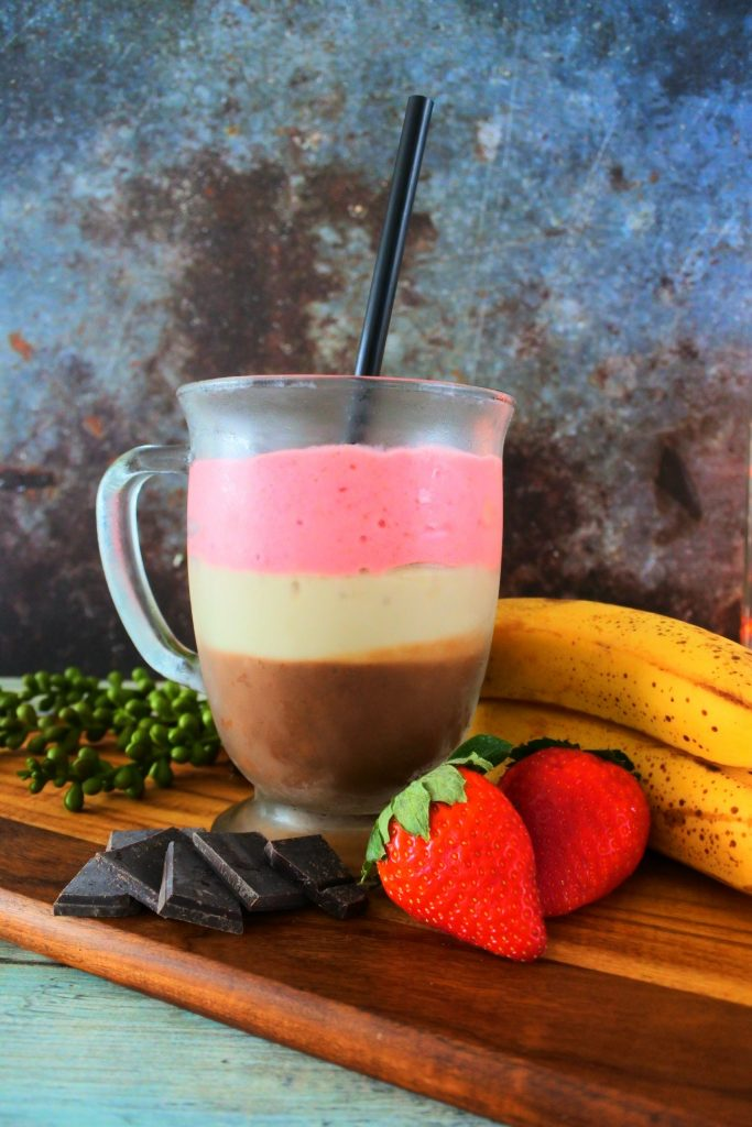 A close up image of a glass mug of Neapolitan Milkshake on a wooden board surrounded by dark chocolate, fresh strawberries and bananas