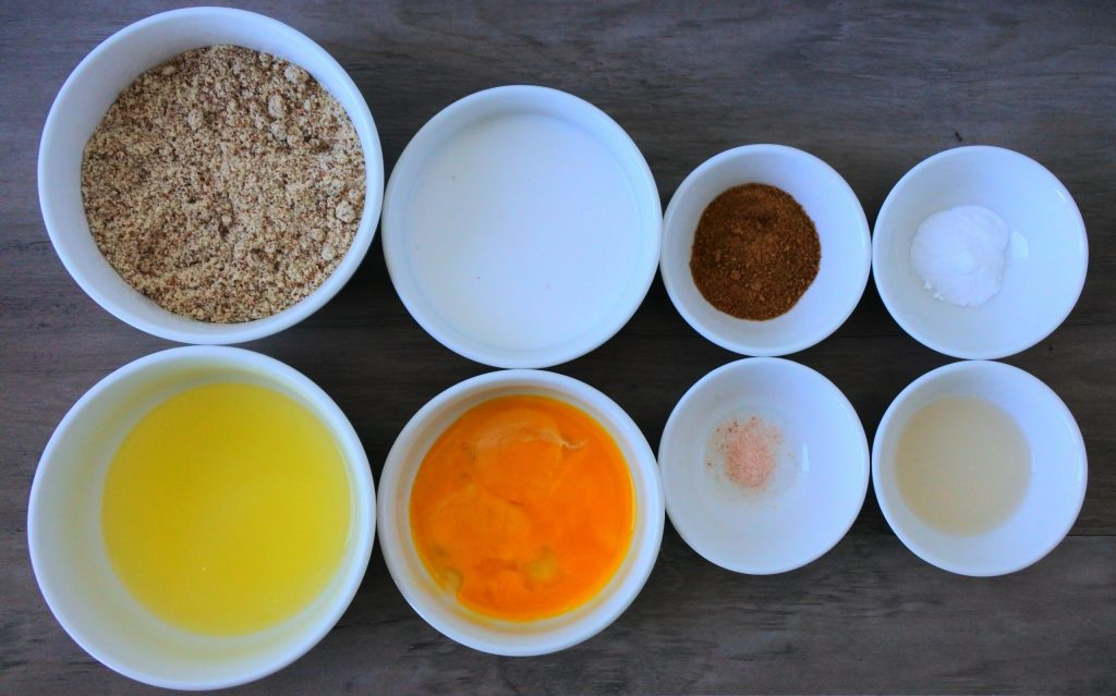 An overhead image of bowls containing individual ingredients for almond flour pancakes including almond flour, separated eggs, coconut milk, coconut sugar, salt, vanilla extract, and baking soda