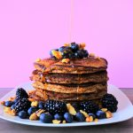 An image of a stack of almond flour pancakes that are topped and surrounded by fruit and nut with a stream of maple syrup being poured onto it.