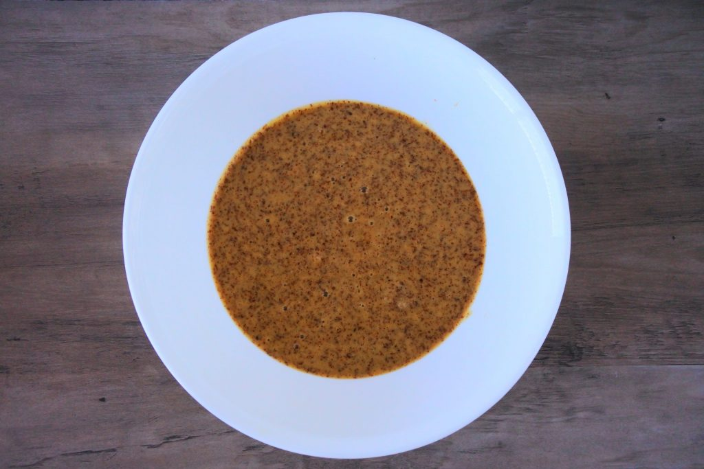An overhead image of a bowl containing a mixture of almond flour, salt, and baking soda, egg yolks, coconut sugar, coconut milk, and vanilla