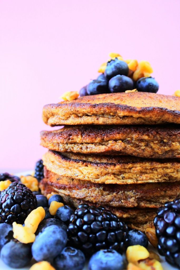A vertical head-on image of a close up shot of a stack of pancakes topped and surrounded by chopped walnuts, blackberries and blueberries.