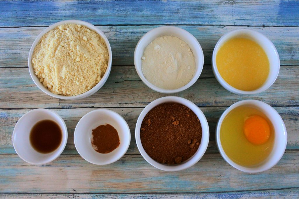 An overhead image of bowls of ingredients for almond flour pie crust including: blanched almond flour, coconut flour, melted butter, and egg, coconut sugar, cinnamon and vanilla extract