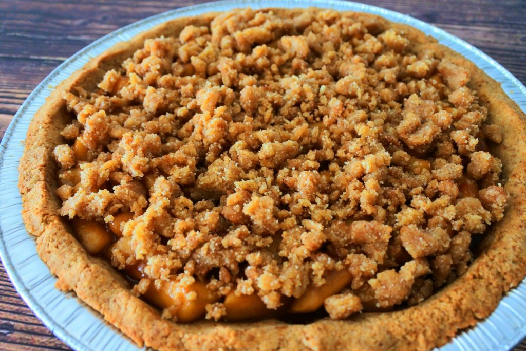A close up image of an apple pie with an unbaked almond flour crumble top