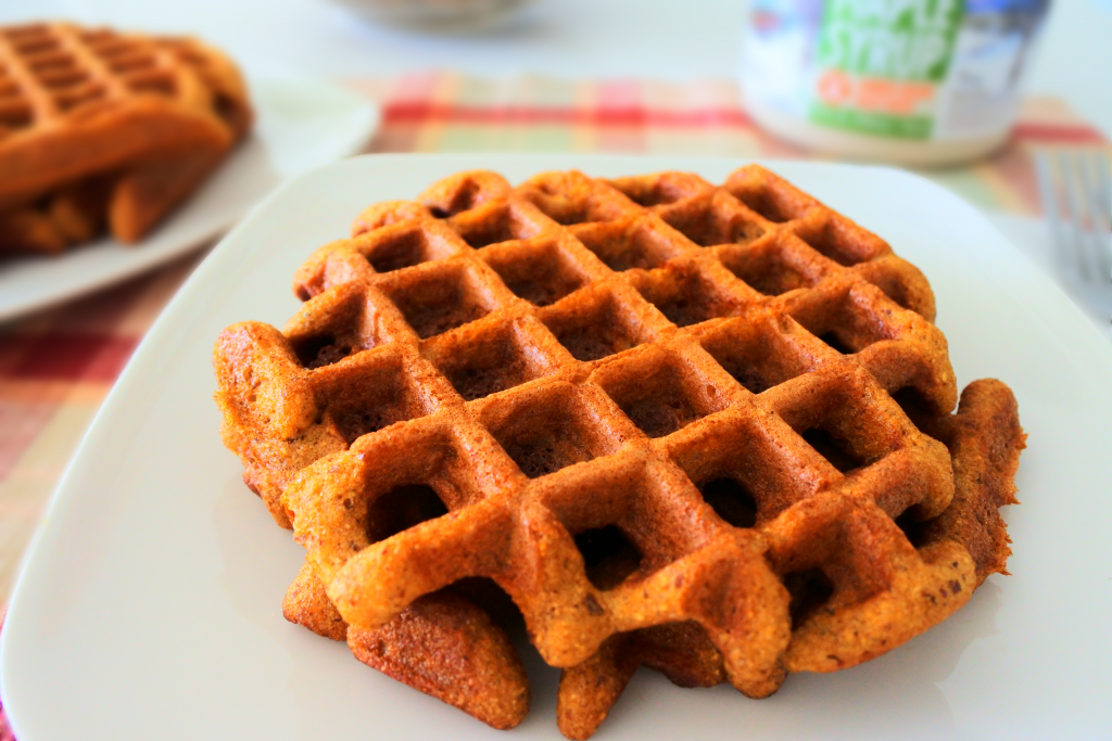 A close up image of almond flour waffles on a plate with a second plate of waffles and a bottle of maple syrup in the background.