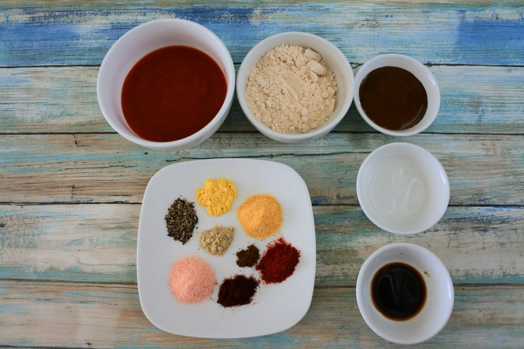 An overhead image of ingredients for a homemade bbq sauce including tomato sauce, sugar, molasses, vinegar, worcestershire sauce and various spices