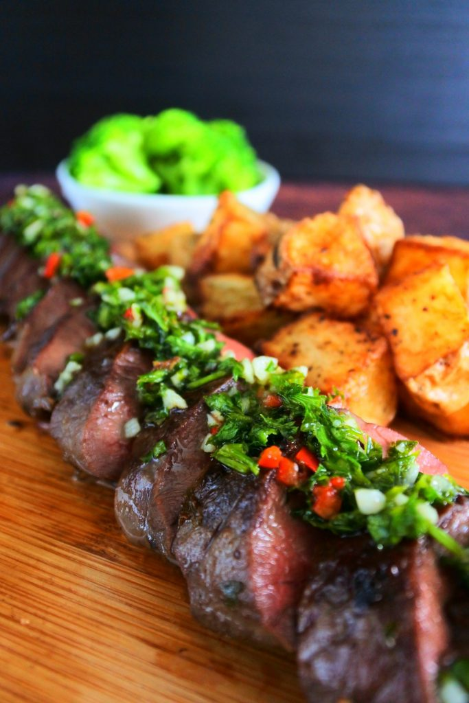 A close up image of sliced grilled beef heart done medium and topped with a chimichurri sauce with fried potatoes and a small dish of broccoli in the background