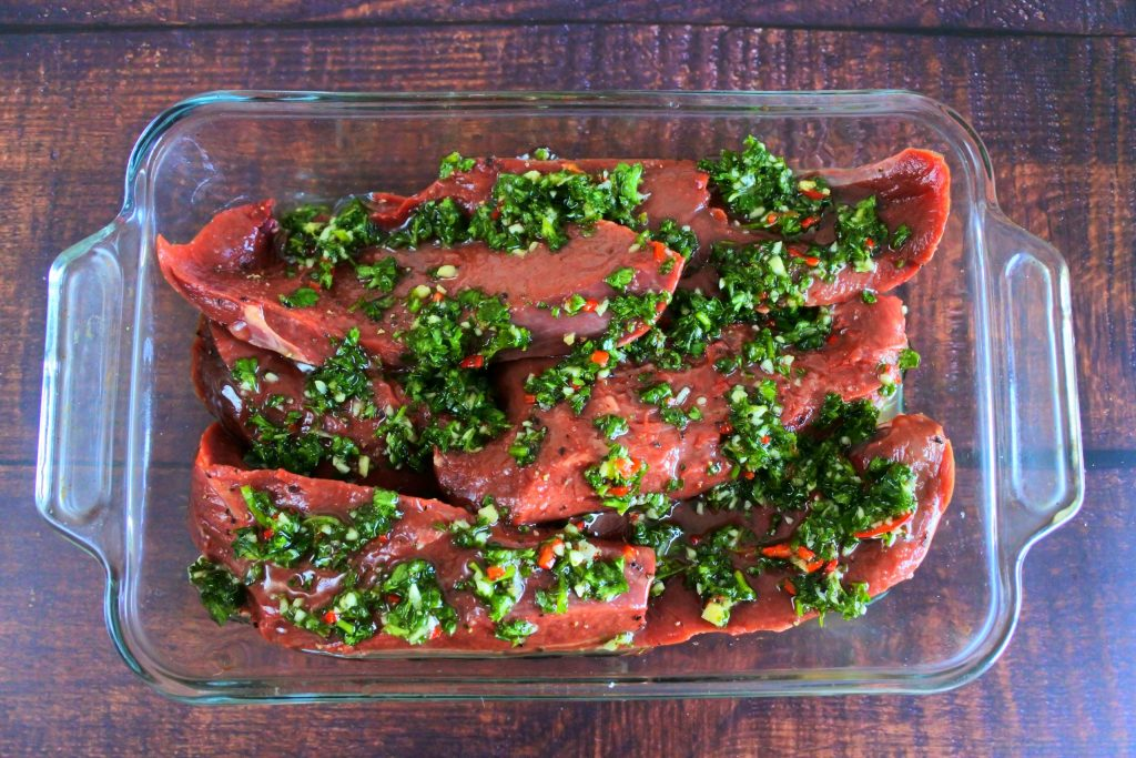 An overhead image of a glass dish of raw beef heart steaks marinating in a chimichurri sauce