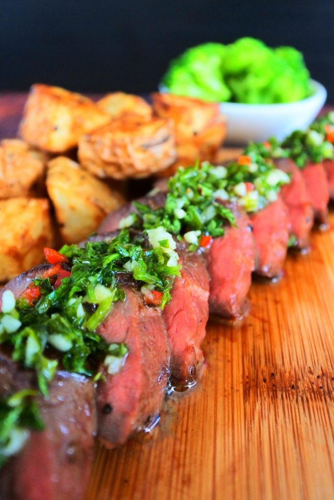 A close up image of sliced grilled beef heart done medium-rare and topped with a chimichurri sauce with fried potatoes and a small dish of broccoli in the background