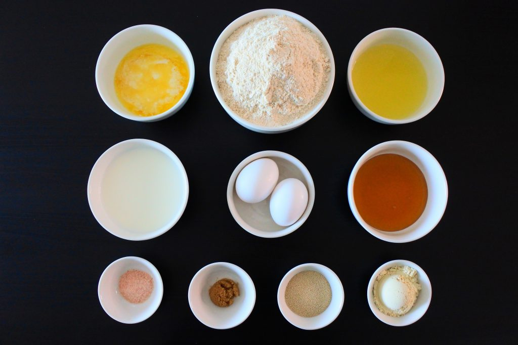 An overhead image of an assortment of bowls containing ingredients such as: Butter, milk, salt, raw brown sugar, yeast, eggs, white whole wheat flour, pineapple juice, honey, and vital wheat gluten