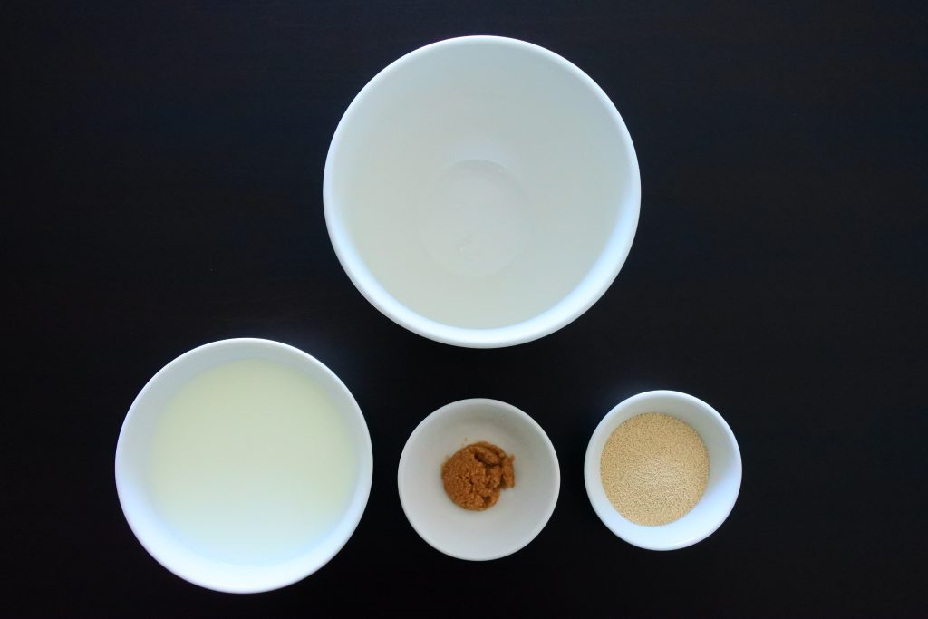 An overhead image of four bowls, one larger empty one, one containing milk, another containing sugar and the last containing yeast