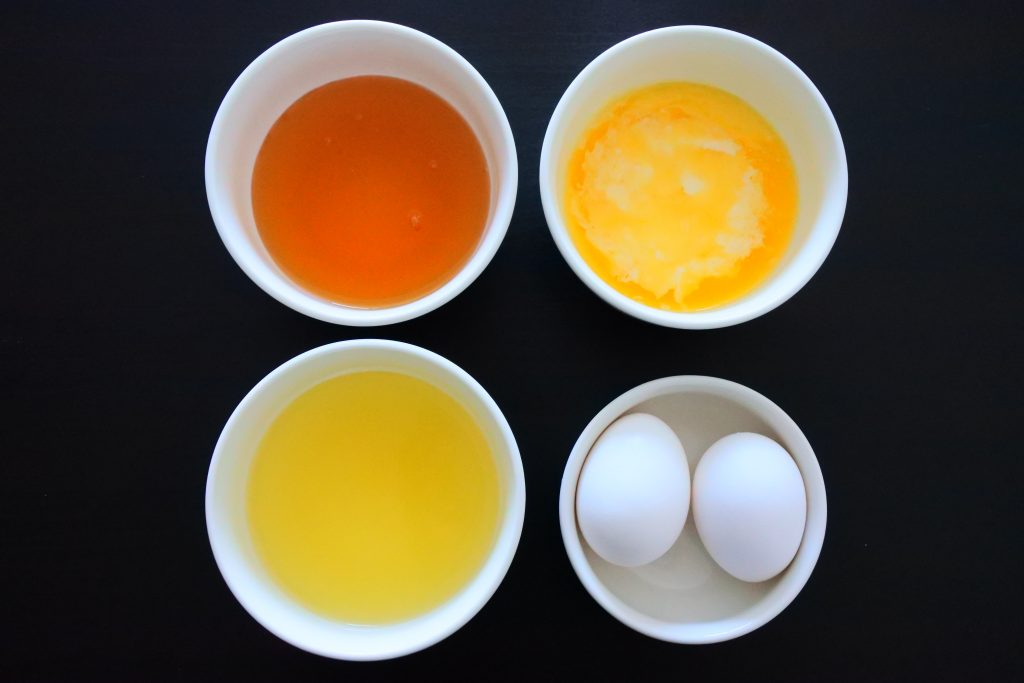 An overhead image of four bowls containing honey, melted butter, pineapple juice and eggs