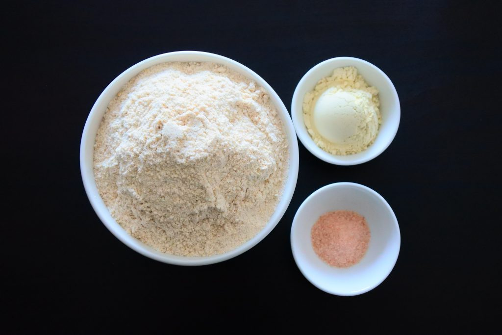 An overhead image of three bowls containing whole wheat flour, vital wheat gluten and salt