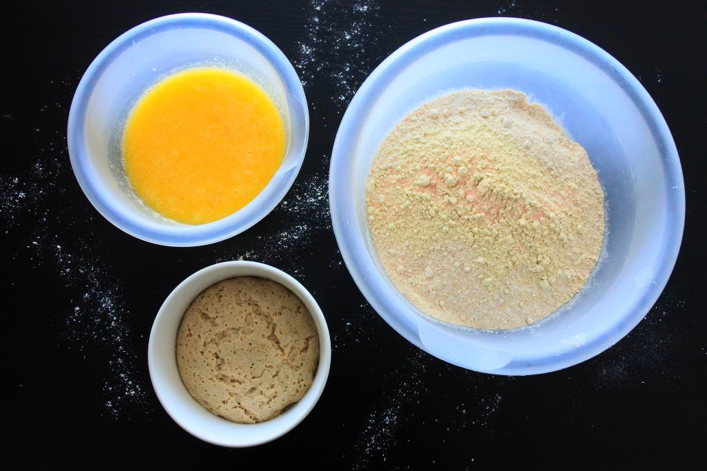 An overhead image of three bowls: one containing whole wheat flour, vital wheat gluten and salt, the other containing activated yeast and the third containing egg, honey, pineapple juice and melted butter
