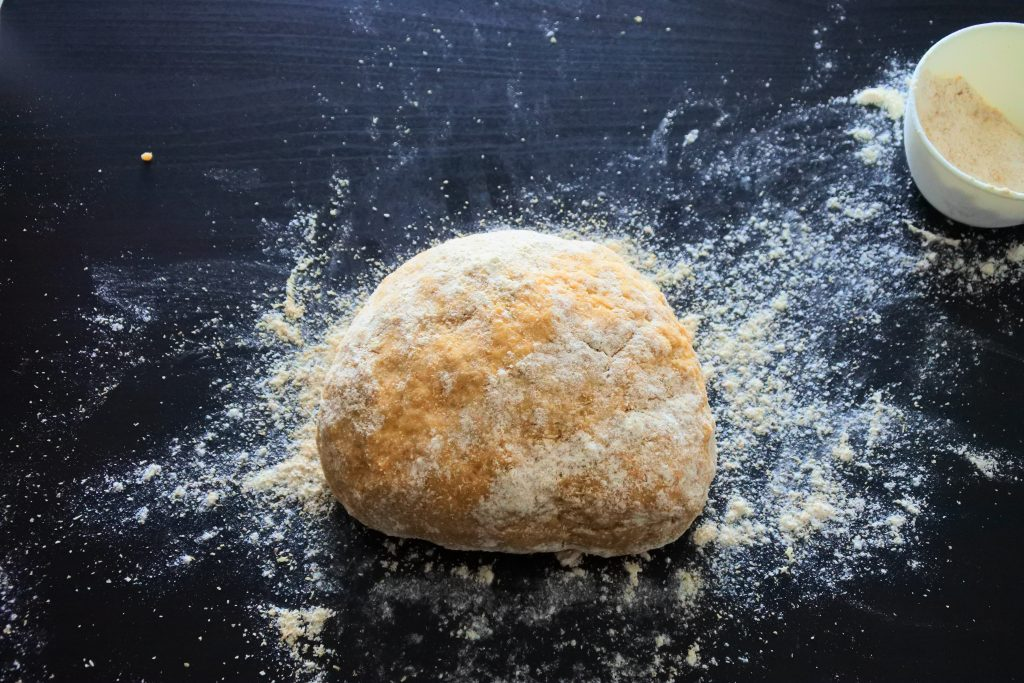 An angled image of floured bread dough on a floured work surface