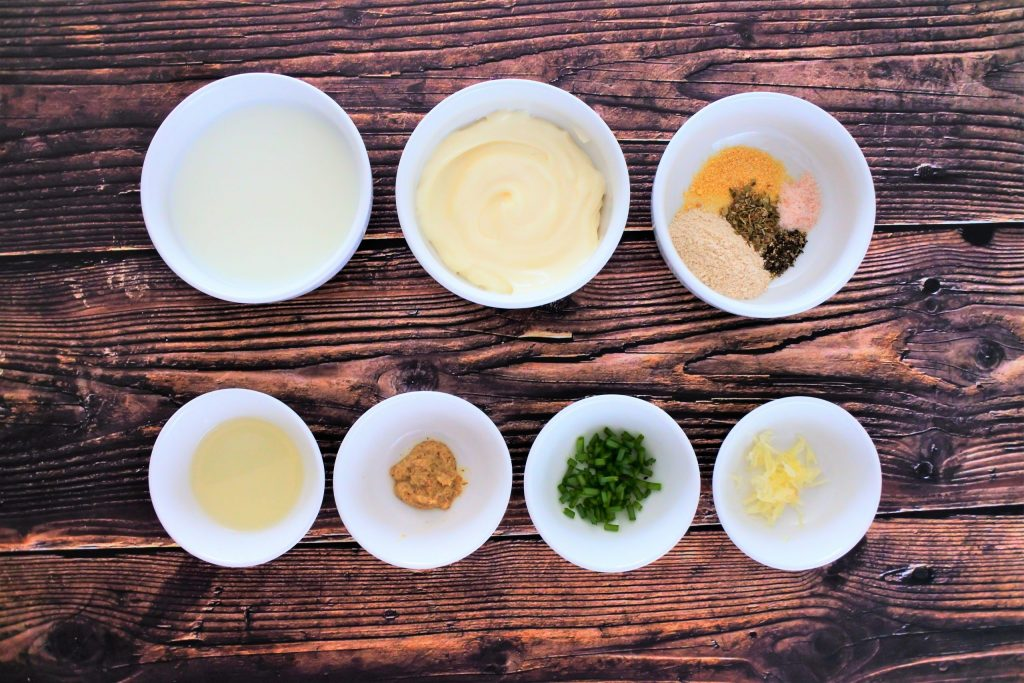 An overhead image of bowls of ingredients for a dressing for broccoli slaw including: whole milk, homemade mayonnaise, spices, lemon juice, mustard, chives and garlic