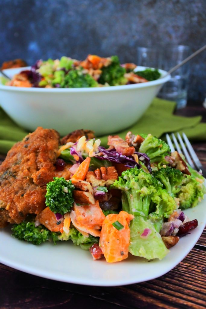 A close up image of a plate of broccoli salad with a piece of parmesan crusted chicken with a larger bowl of broccoli salad in the background