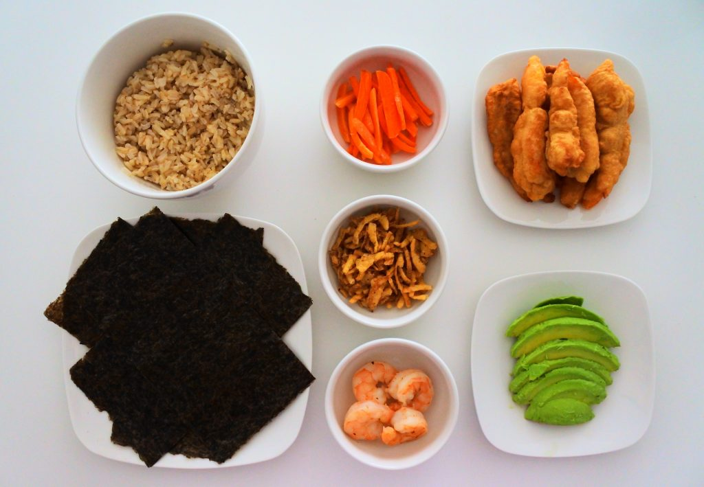 An overhead image of an assortment of ingredients including brown rice, nori (seaweed) sheets, julienne carrots, tempura fried onions bits, quick boil shrimp, tempura fried shrimp and sliced avocados.