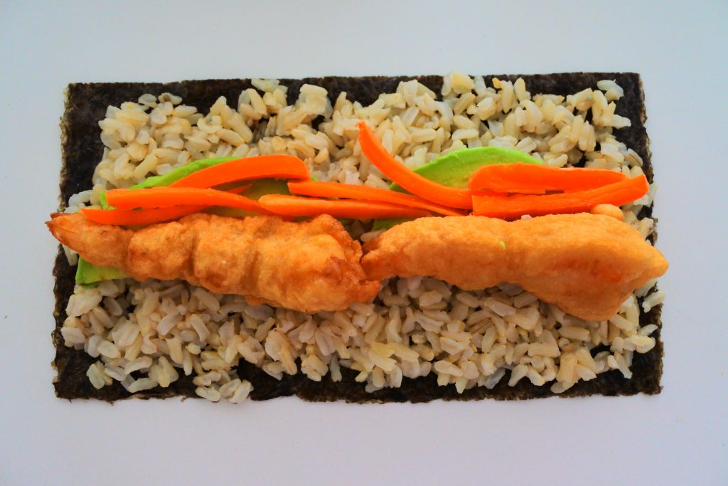 An overhead view of a halfsheet of nori topped with brown rice, avocado, carrots and two tempura fried shirmp
