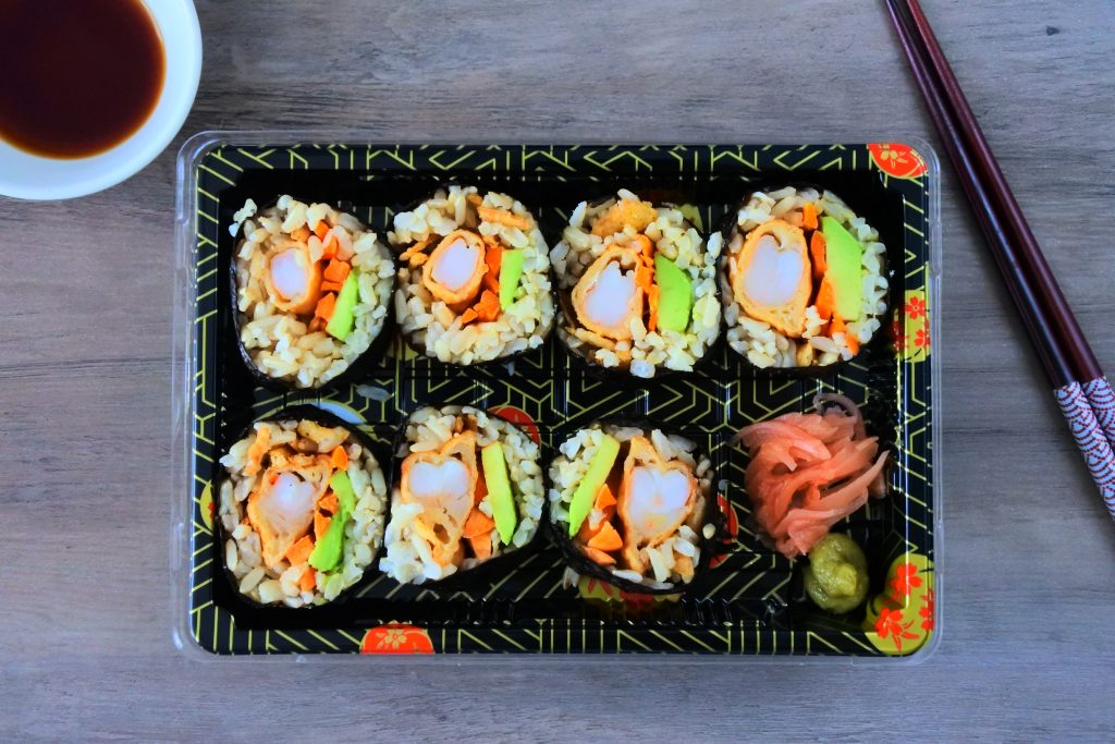 An overhead image of a container holding pieces of shrimp tempura sushi with pickled ginger and wasabi paste on the side, with a bowl of soy sauce in the top left corner and a pair of chopsticks on the top right.