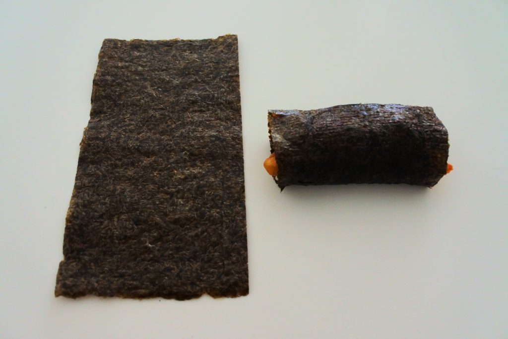A tilted angle image of a half-sheet of sushi nor (seaweed) turned length-ways next to a shorter rolled sushi roll