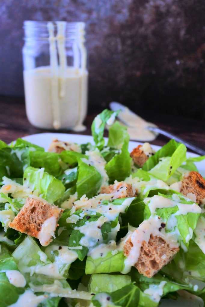 A head on image of a dressed Caesar salad with a bottle of homemade Caesar Salad Dressing in the background.