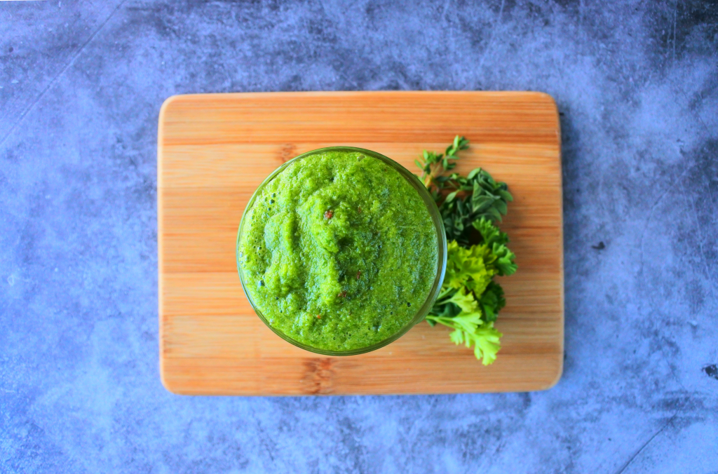 An over head image of a jar of fresh green seasoning on a wooden board with fresh herbs at the base