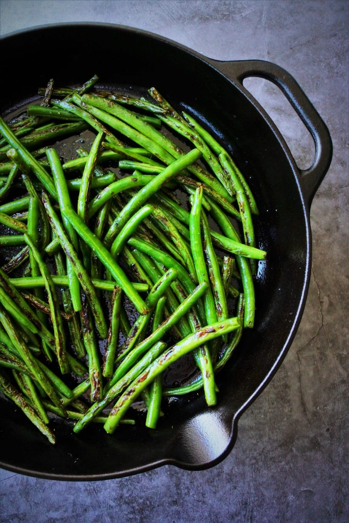 An overhead image of a part of a cast iron skillet of charred green beans