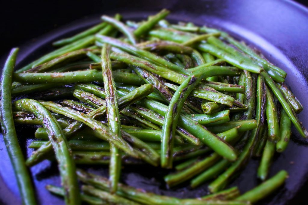 A close up image of charred green beans in a cast iron skillet