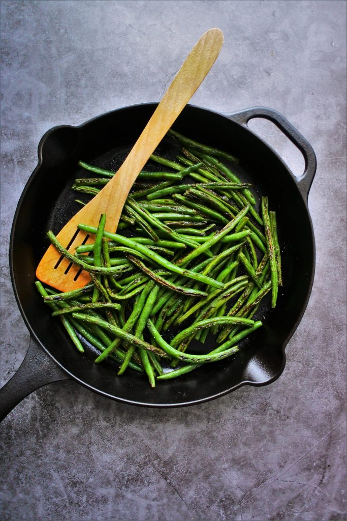 An overhead image of a cast iron skillet of charred green beans with a wooden utensil in it