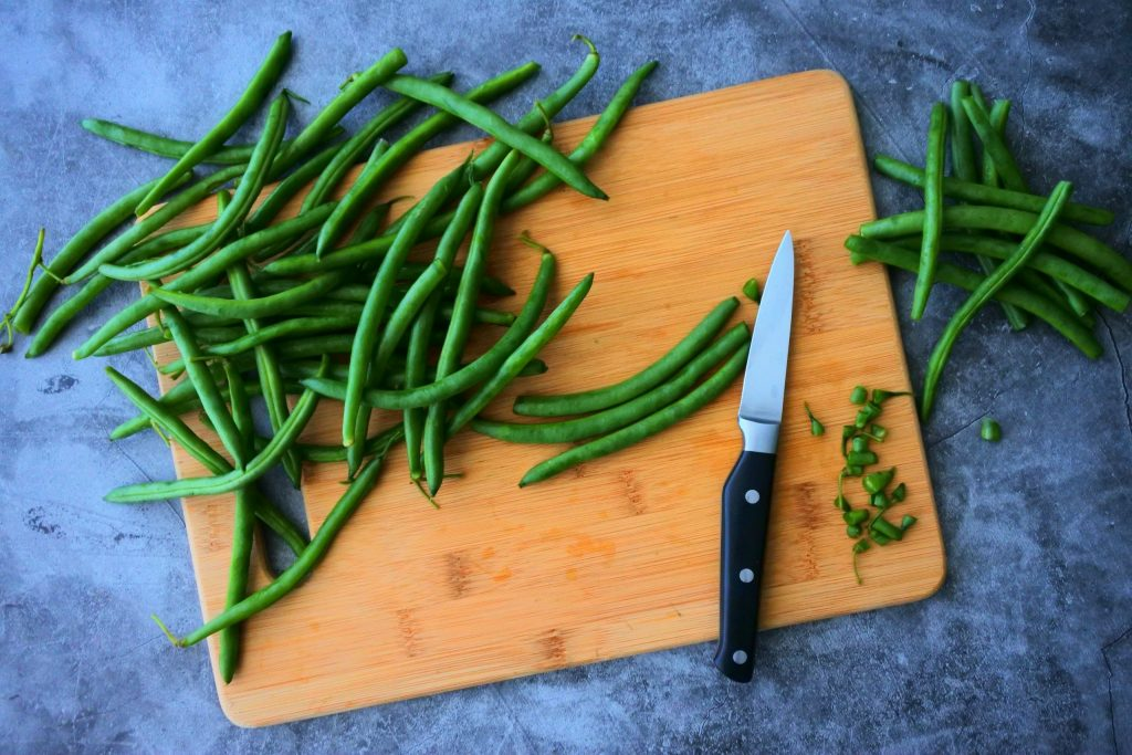 An overhead image of green beans being prepped and their tips being cut off.