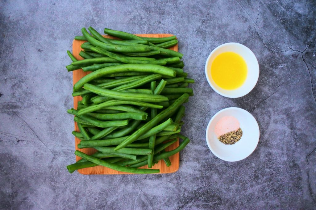 An overhead image of ingredients needed for skillet charred green beans including green beans, melted butter, salt and pepper.