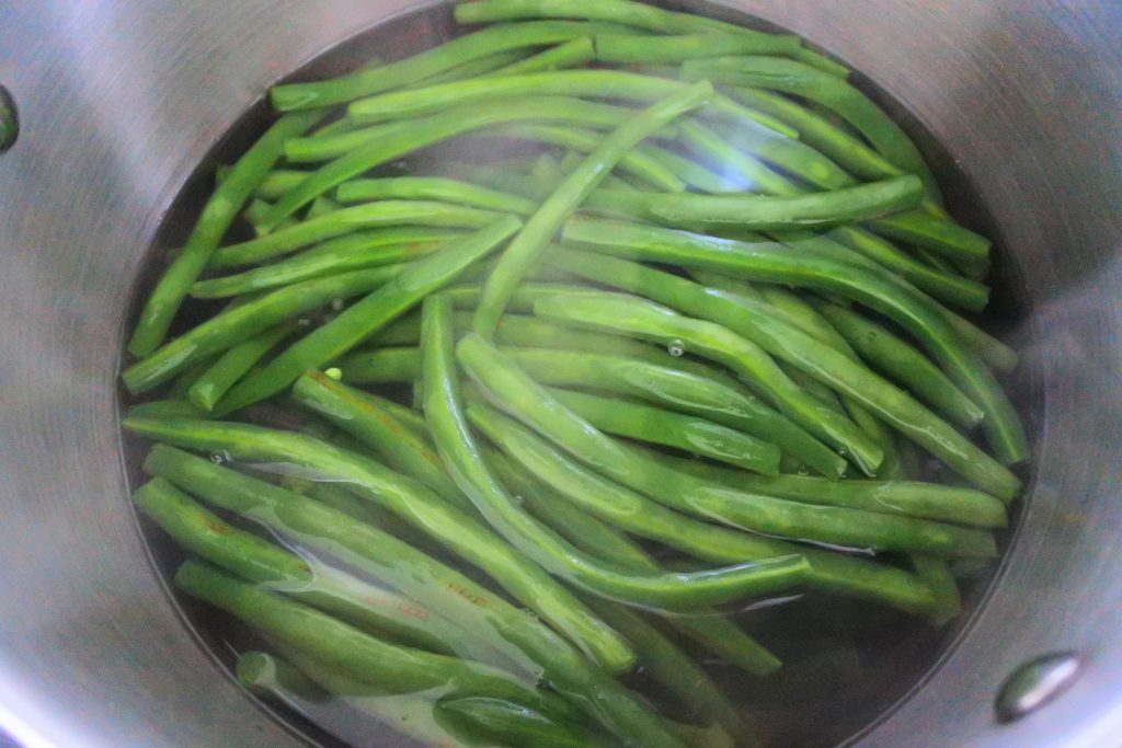An overhead image of green beans in a pot of boiling water