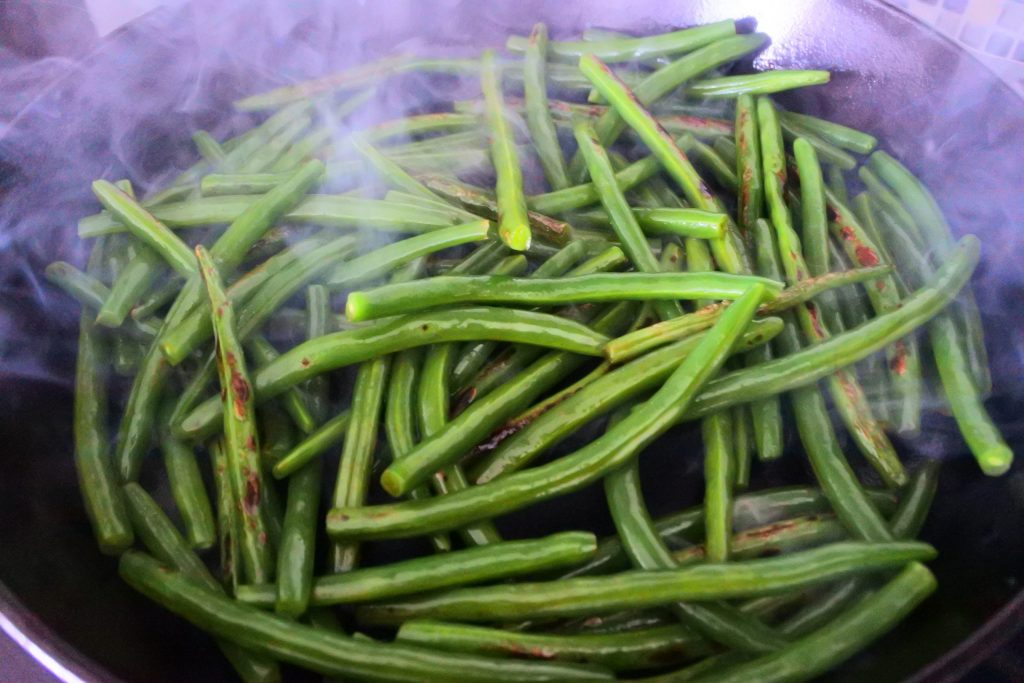 An angled image of smoky green beans in a cast iron skillet