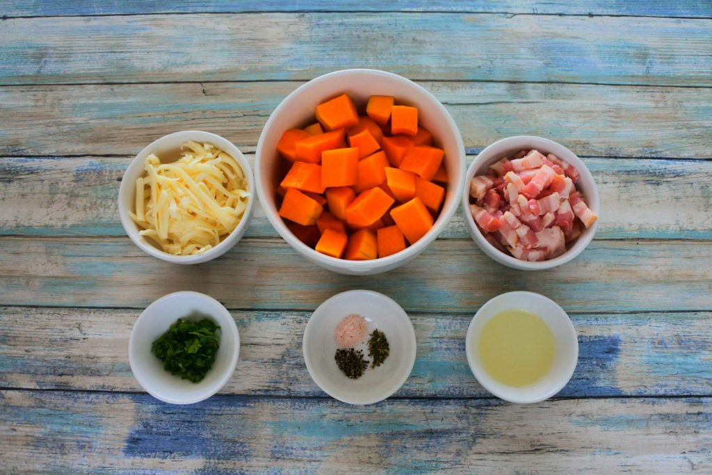 An overhead image of bowls of ingredients including shredded cheese, cubed butternut squash, bacon pieces, light olive oil, salt, black pepper and oregano, and fresh parsley