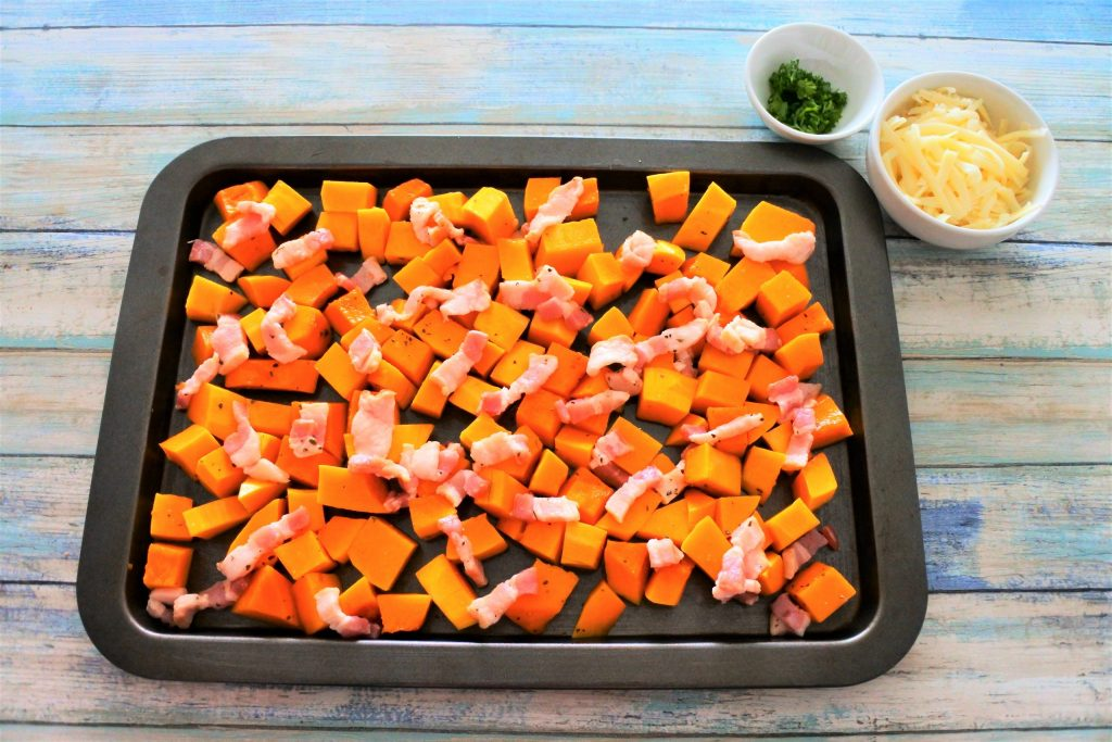 An overhead image of a baking tray with cubed butternut squash and bacon pieces with a small dish of fresh parsley and another dish of shredded cheese in the right corner