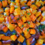 An overhead tilt shifted image of cheesy bacon oven roasted butternut squash on a baking tray topped with fresh parsley
