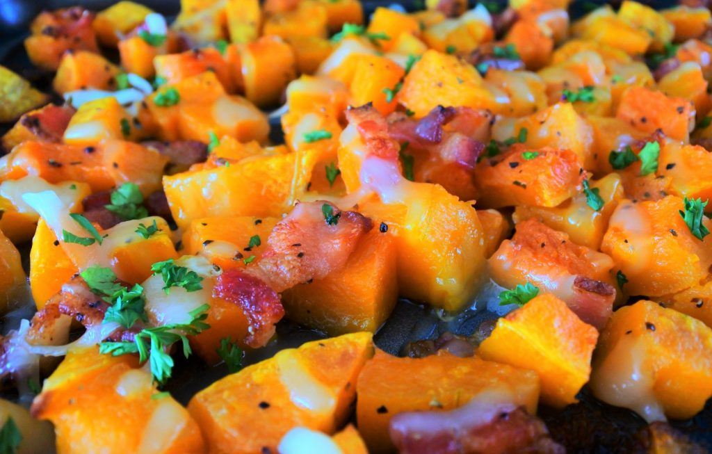 An close up image of cheesy bacon oven roasted butternut squash on a baking tray topped with fresh parsley