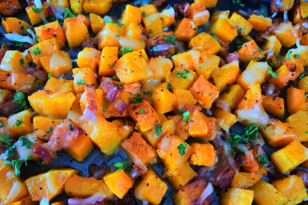 An overhead image of cheesy bacon oven roasted butternut squash on a baking tray topped with fresh parsley