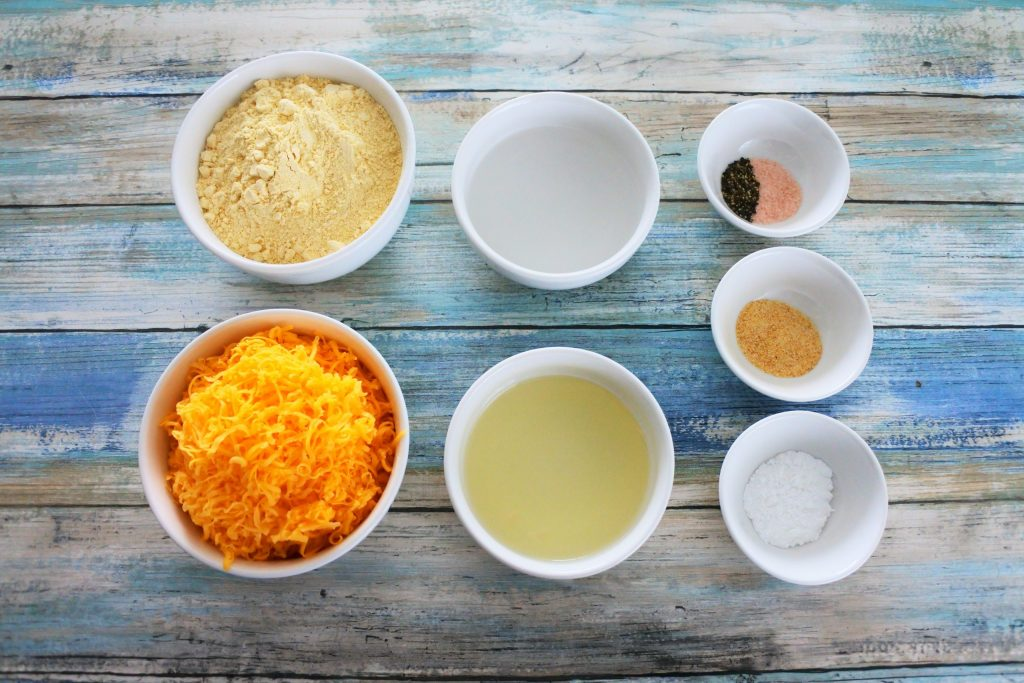 An overhead image of bowls of ingredients for cheesy chickpea crackers including: chickpea flour, shredded cheddar cheese, water, light olive oil, salt, pepper, garlic powder and baking powder