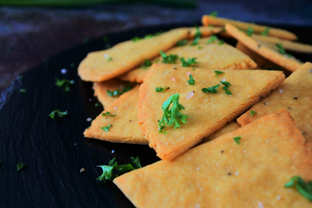 A head on image of a pile of cheesy chickpea crackers topped with coarse salt and fresh parsley