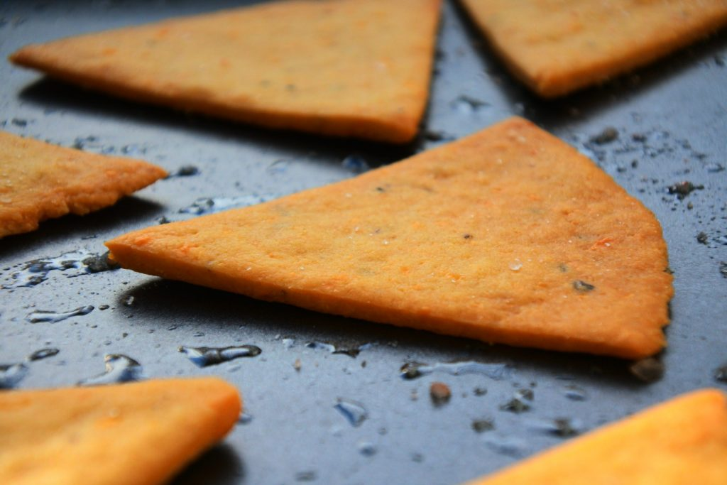 A close up image of a baked chickpea cracker on a baking tray
