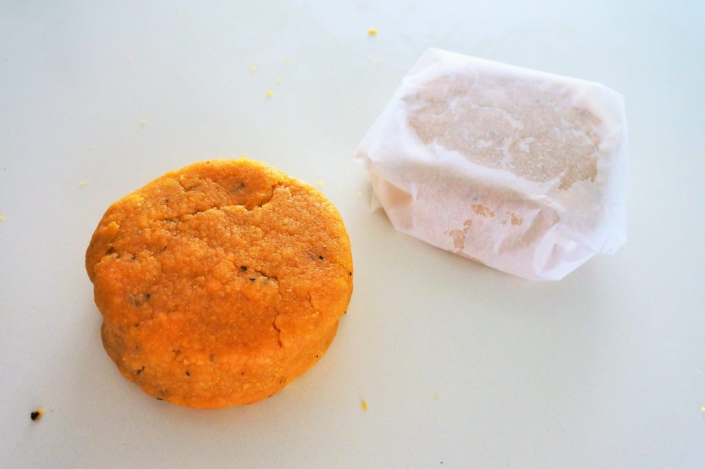 An overhead image of chickpea cracker dough formed into a disc with another one wrapped in parchment paper