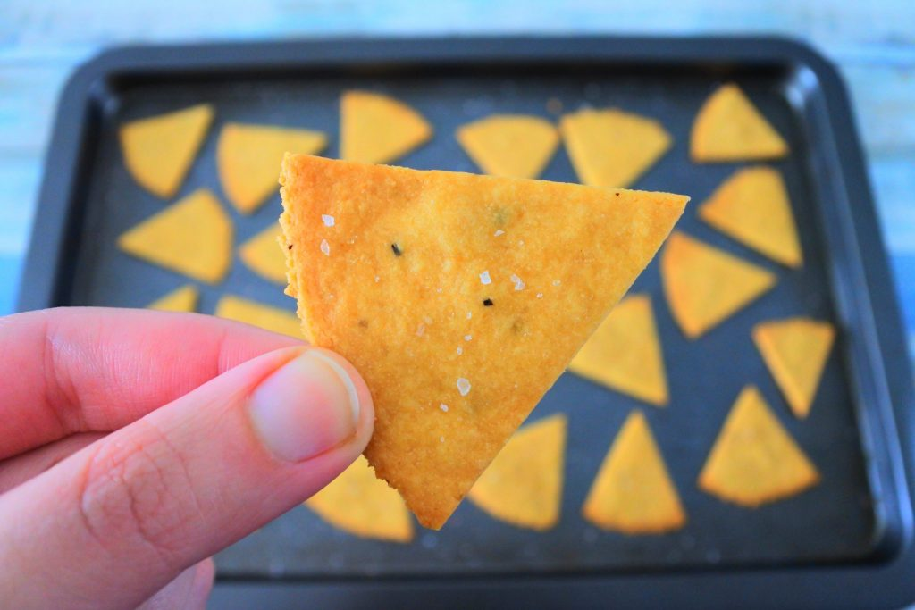A close up image of a cheesy chickpea cracker being held