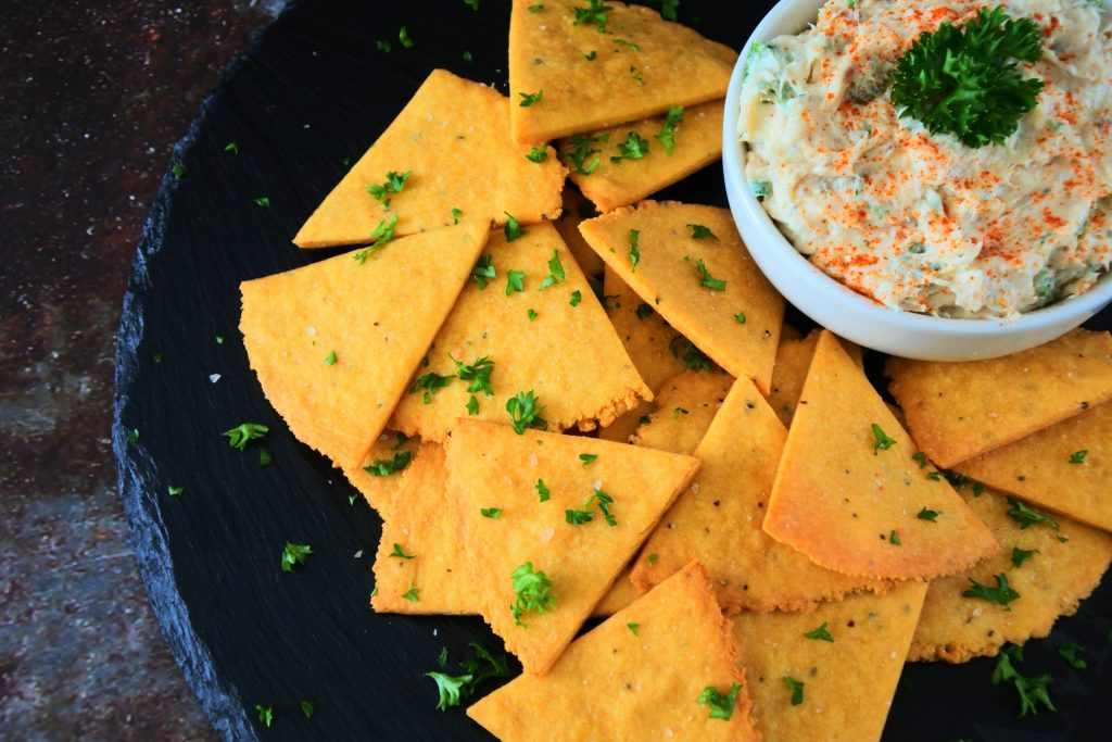 An overhead image of a plate of cheesy chickpea crackers topped with coarse pink salt and fresh parsley with a small dish of creamy dip
